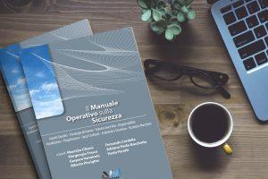 """Libro """"Il Manuale Operativo sulla Sicurezza"""" suscrivania color legno, tazza di. caffe, occhiali, pianta e computer"""